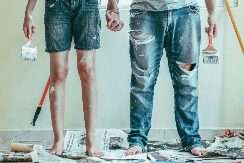 Couple Stood In Shorts And Jeans, Painbrush In Either Hand And A Paintroller In The Background