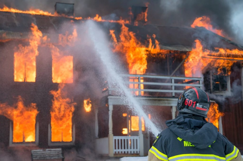 Person Extinguishing A House Fire