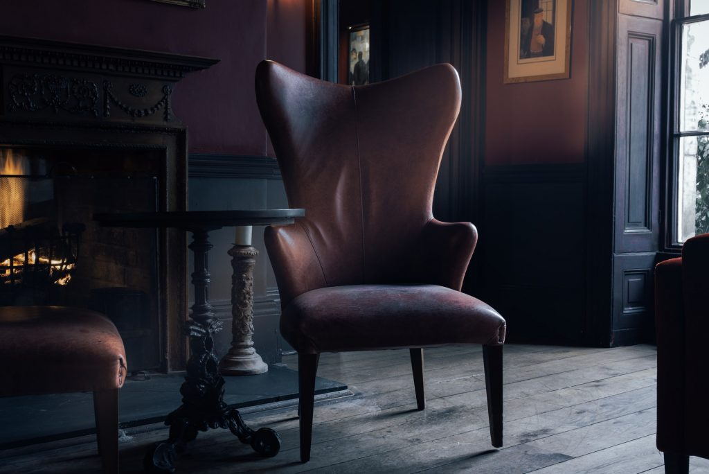 Two Leather Chairs In A Dimly Lit Room