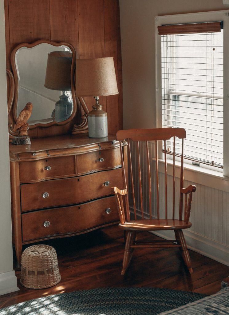 Wooden Rocking Chair With A Wooden Chest Of Drawers Beside It And A Wooden Framed Mirror