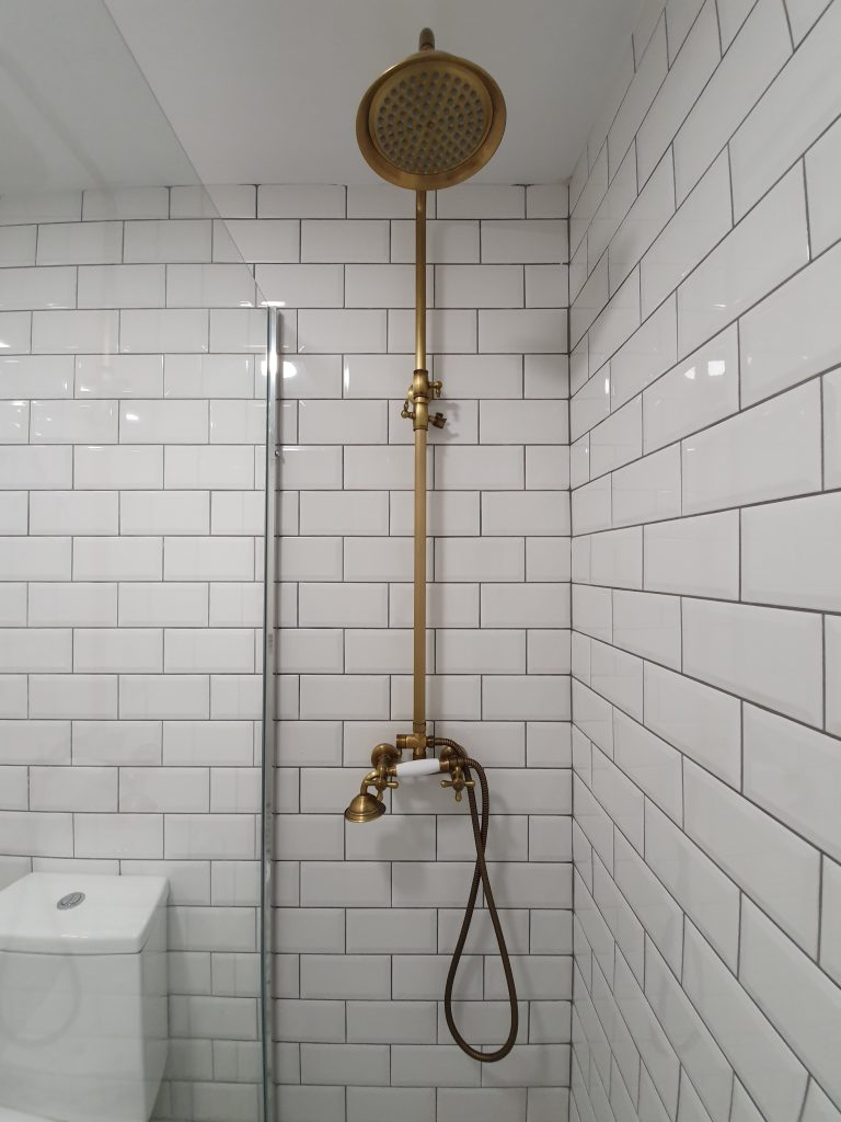 Brass Shower Withg White Tiling And A Clear Glass Protective Frame