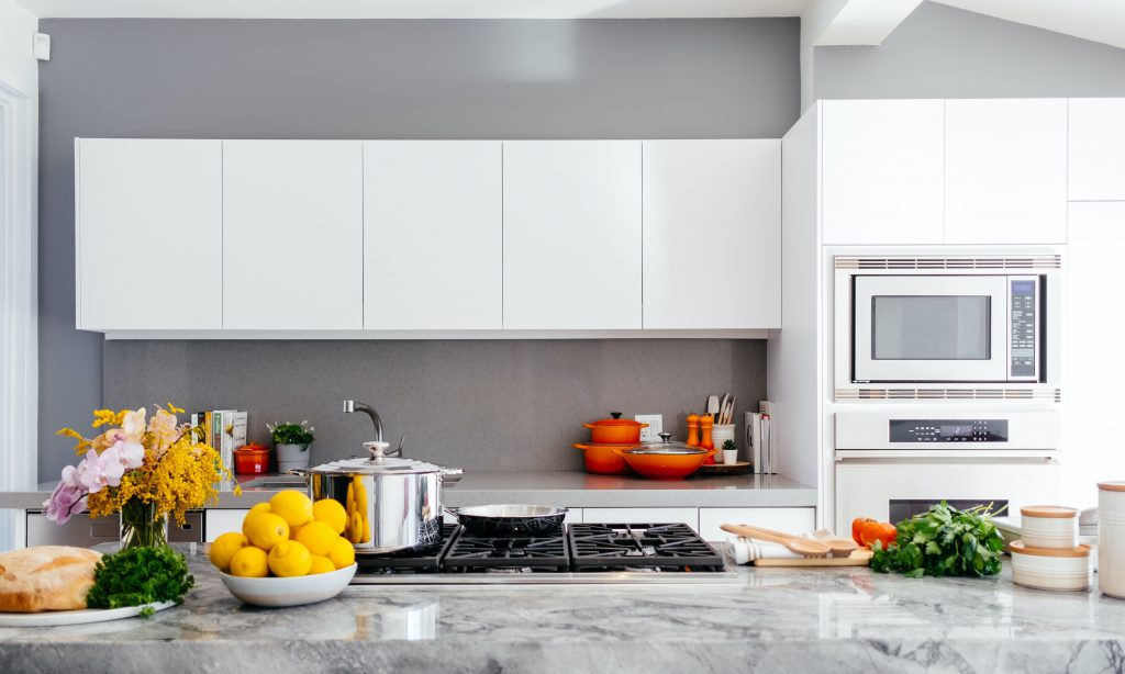 Grey And White Kitchen With Plenty Going On, Fruit, Bread, Stovetop, Microwave Oven And Lemons