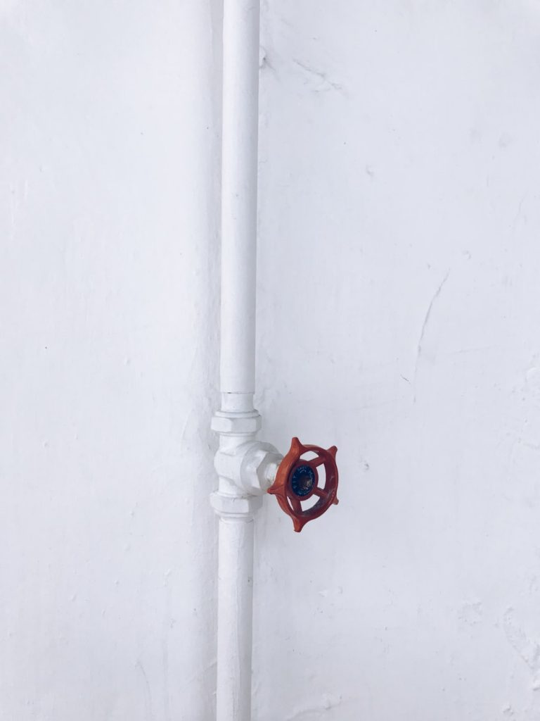 White Wall With A Matching White Pipe And Red Lever Valve
