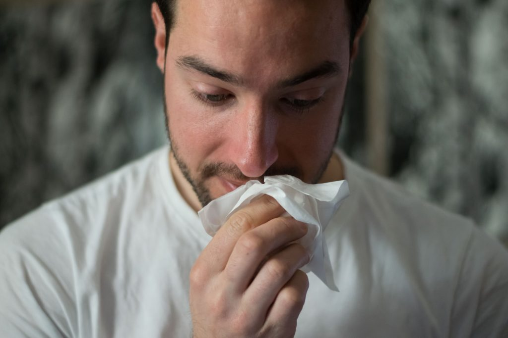 Sick Man In White Tshirt Wiping Face And Nose