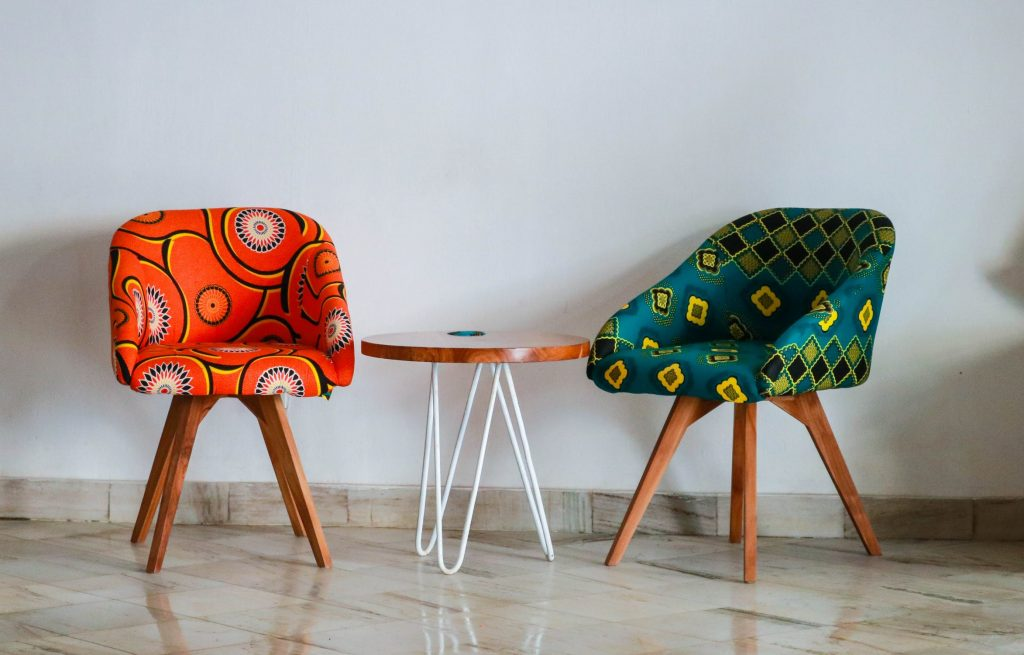 Two Assorted Color Chairs Next To A Small Side Table