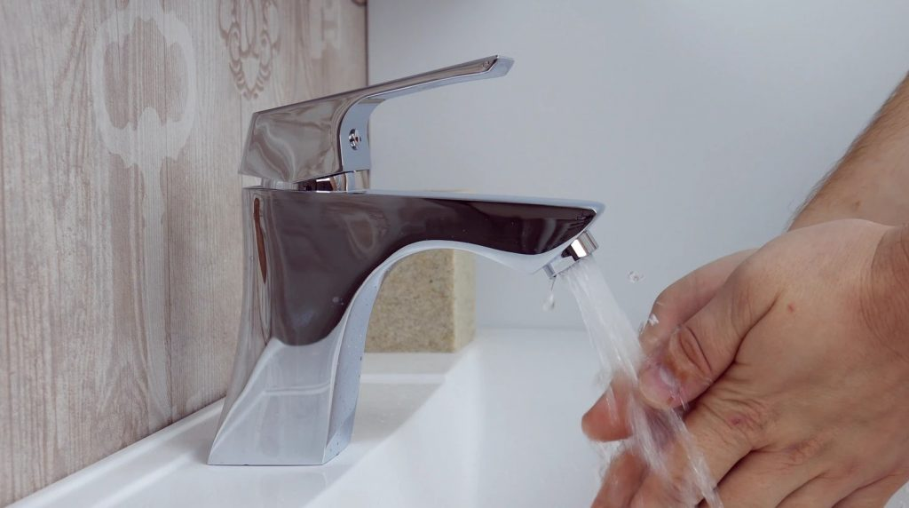 Person Washing Their Hands Using A Stainless Steel Faucet