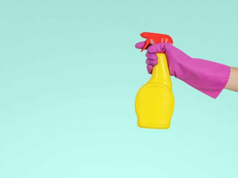 Person Holding Yellow Spray Bottle