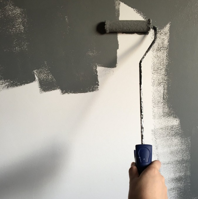Person Painting White Wall With Gray Paint Roller