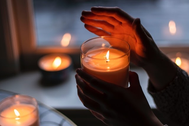 Person Holding Lit Candle