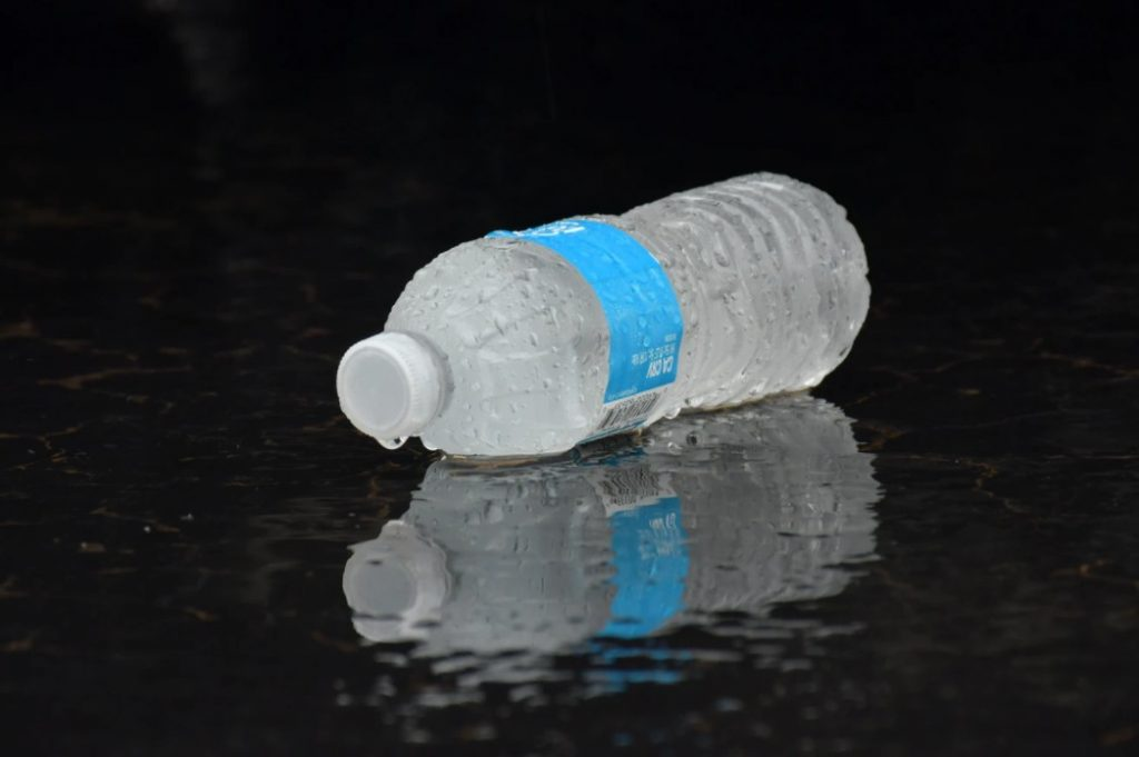 Plastic Water Bottle In Puddle