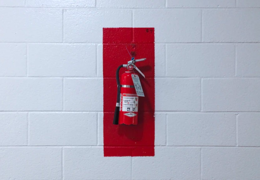 Red Fire Extinguisher Mounted In White Painted Wall