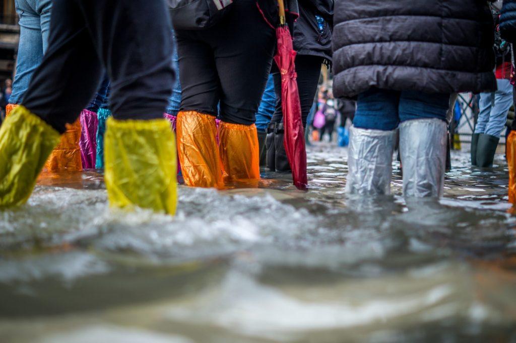 People Walking In Flooded Street